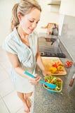 Mulher nova que faz a salada Fotografia de Stock Royalty Free