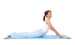 A mulher nova que fazem a ioga ou os pilates exercitam na esteira Fotografia de Stock Royalty Free