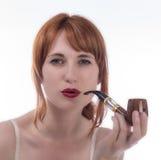 Mulher nova que fuma uma tubulação Foto de Stock Royalty Free