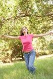 Mulher nova que funciona através do parque Fotos de Stock Royalty Free