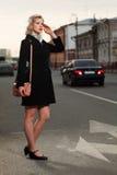 Mulher nova que graniza um táxi de táxi Fotos de Stock Royalty Free