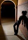 Mulher nova que inclina-se de encontro à parede de tijolo na noite Fotografia de Stock Royalty Free