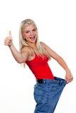 Mulher nova que indica o sucesso da perda de peso Foto de Stock Royalty Free