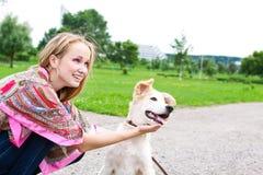 Mulher nova que joga com o filhote de cachorro ao ar livre Imagem de Stock