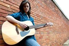 Mulher nova que joga a guitarra Imagem de Stock