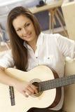 Mulher nova que joga a guitarra Fotografia de Stock Royalty Free