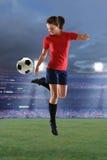 Mulher nova que joga o futebol foto de stock