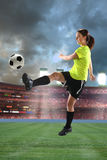 Mulher nova que joga o futebol imagem de stock