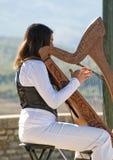 Mulher nova que joga uma harpa Foto de Stock