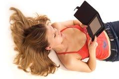 Mulher nova que lê o livro eletrônico fotografia de stock