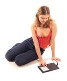 Mulher nova que lê o livro eletrônico Foto de Stock Royalty Free