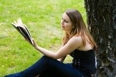 Mulher nova que lê um livro. Imagens de Stock Royalty Free