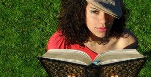 Mulher nova que lê um livro   Foto de Stock