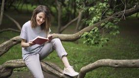 Mulher nova que lê um livro em um parque video estoque