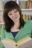 Mulher nova que lê um livro na biblioteca Foto de Stock Royalty Free