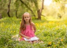 Mulher nova que lê um livro no parque fotos de stock royalty free