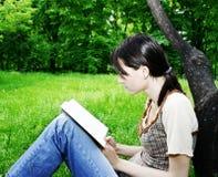 Mulher nova que lê uma novela foto de stock royalty free