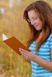 Mulher nova que lê o livro alaranjado Fotos de Stock Royalty Free