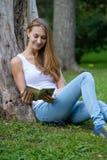 Mulher nova que lê um livro no parque Imagens de Stock