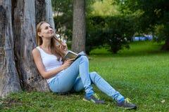 Mulher nova que lê um livro no parque Fotografia de Stock Royalty Free