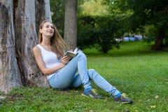 Mulher nova que lê um livro no parque Foto de Stock Royalty Free