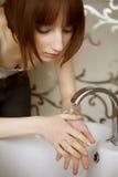 Mulher nova que lava sua face fotografia de stock