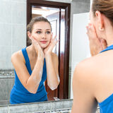 Mulher nova que lava sua face Imagens de Stock