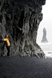 Mulher nova que levanta na praia preta da areia perto de Vik Foto de Stock Royalty Free