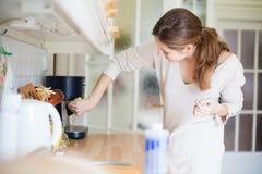 Mulher nova que limpa a cozinha Foto de Stock