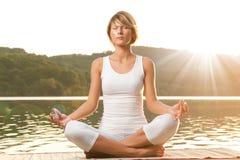 Mulher nova que meditating no lago Imagem de Stock