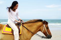 Mulher nova que monta um cavalo Foto de Stock