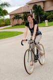 Mulher nova que monta uma bicicleta Imagens de Stock