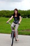 Mulher nova que monta uma bicicleta Imagem de Stock