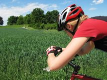 Mulher nova que monta uma bicicleta Fotos de Stock