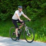 Mulher nova que monta uma bicicleta na estrada através da floresta Fotos de Stock Royalty Free