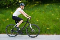 Mulher nova que monta uma bicicleta na estrada através da floresta Imagem de Stock