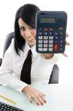 Mulher nova que mostra a calculadora Fotos de Stock