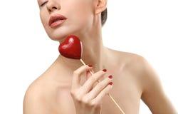 Mulher nova que mostra doces dados forma coração. Fim da face Fotografia de Stock
