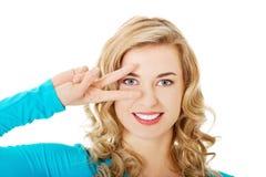 Mulher nova que mostra o sinal da vitória Fotografia de Stock Royalty Free