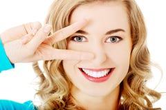 Mulher nova que mostra o sinal da vitória Imagens de Stock Royalty Free