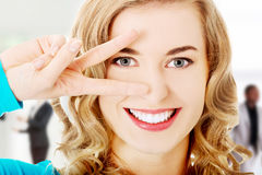 Mulher nova que mostra o sinal da vitória Imagem de Stock Royalty Free