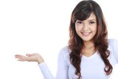 Mulher nova que mostra um produto imaginário Fotos de Stock Royalty Free