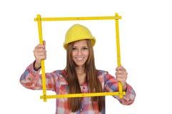 Mulher nova que olha através de uma régua amarela Imagens de Stock