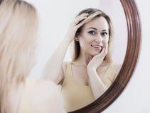 Mulher nova que olha no espelho Fotografia de Stock