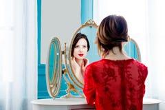 Mulher nova que olha o espelho imagens de stock