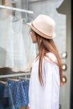 Mulher nova que olha o indicador da loja imagens de stock royalty free