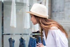 Mulher nova que olha o indicador da loja foto de stock royalty free