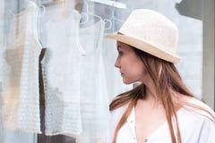 Mulher nova que olha o indicador da loja fotografia de stock royalty free