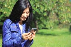 Mulher nova que olha o telefone. Imagens de Stock Royalty Free