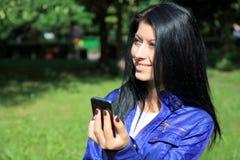 Mulher nova que olha o telefone e o sorriso Imagem de Stock Royalty Free